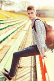 Fashion young man with backpack in city at sunny Royalty Free Stock Photos
