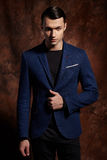 Fashion young man blue suit on brown background Stock Images