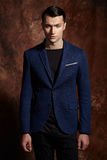 Fashion young man blue suit on brown background Stock Image