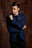 Fashion young man blue suit on brown background Stock Photo