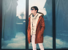 Fashion young man in the city wearing a jacket over urban glass background Royalty Free Stock Images