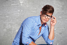 Fashion young man holding his glasses Royalty Free Stock Images