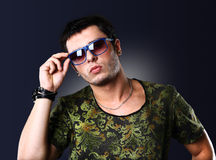 Fashion young man holding his fashionable sunglasses Stock Image