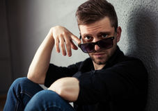 Fashion young man holding his fashionable sunglasses on gray Royalty Free Stock Photography