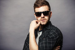 Fashion young man holding his fashionable sunglasses on gray Royalty Free Stock Photo