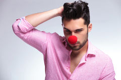 Fashion young man with red nose and hand in hair Stock Image