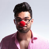 Fashion young man with red nose holds his breath Stock Image