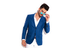 Fashion young man taking off his sunglasses stock photo