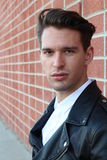 Fashion young man in white shirt and black leather jacket over modern blurred brick wall Stock Photo
