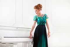 Fashion young pretty redhead lady playing grand piano. Beautiful young attractive woman in dress playing white piano Royalty Free Stock Photography