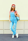 Fashion young pretty woman wearing a denim jumpsuit in the city over white stock photos