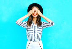 Fashion young smiling woman is closes hides her eyes having fun over colorful blue Royalty Free Stock Image