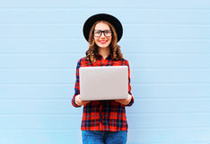 Fashion young smiling woman holding laptop computer in city, wearing black hat red checkered shirt over blue background Royalty Free Stock Images