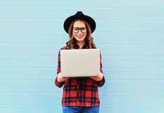 Fashion young smiling woman holding laptop computer in city, wearing a black hat, red checkered shirt over blue background. Fashion young smiling woman holding Stock Photos