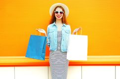 Fashion young smiling woman with a shopping bags, straw hat Royalty Free Stock Photos