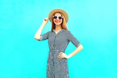 Fashion young smiling woman in striped dress on a blue. Background stock photo