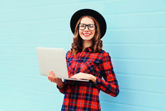 Fashion young smiling woman using laptop computer in city, wearing a black hat, red checkered shirt Stock Photos