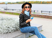 Fashion young smiling woman using smartphone wearing black rock jacket, hat in city Royalty Free Stock Image