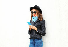 Fashion young smiling woman using smartphone wearing black rock jacket, hat over white Stock Image