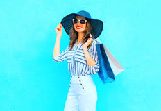 Fashion young smiling woman wearing a shopping bags, straw hat, white pants over colorful blue background posing in city Stock Photos