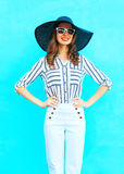 Fashion young smiling woman wearing a white pants and straw summer hat over colorful blue background posing in city Royalty Free Stock Images