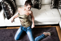 Fashion young woman. Wearing blue jeans and golden corset indoor shot Stock Photography