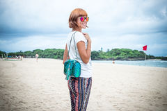 Fashion young woman on the beach. Luxury snakeskin python handbag in her hands. Sunny day. Tropical island Bali Stock Images