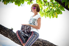 Fashion young woman on the beach. Luxury snakeskin python handbag in her hands. Sunny day. Tropical island Bali Royalty Free Stock Images