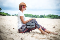 Fashion young woman on the beach. Luxury snakeskin python handbag in her hands. Sunny day. Tropical island Bali Stock Image