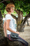 Fashion young woman on the beach. Luxury snakeskin python handbag in her hands. Sunny day. Tropical island Bali Royalty Free Stock Image