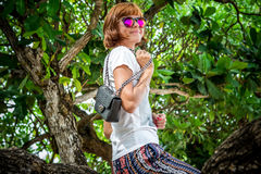 Fashion young woman on the beach. Luxury snakeskin python handbag in her hands. Sunny day. Tropical island Bali Royalty Free Stock Photography