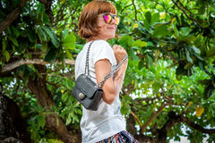 Fashion young woman on the beach. Luxury snakeskin python handbag in her hands. Sunny day. Tropical island Bali Stock Photography