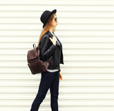 Fashion young woman in black rock style walking in city over white background view profile Stock Photos
