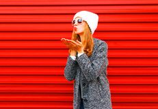 Fashion young woman blowing red lips sends an air kiss on a empty. Background Royalty Free Stock Images