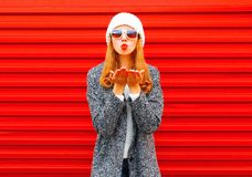 Fashion young woman blowing red lips sends an air kiss Stock Photo