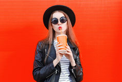 Fashion young woman drinks fresh fruit juice from cup in black rock style having fun over colorful red Stock Photos