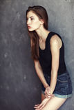 Fashion young woman on grunge wall background Stock Images