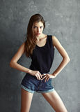 Fashion young woman on grunge wall background Stock Photography