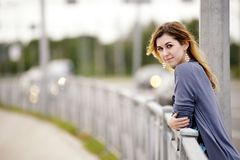 Fashion young woman with hand on handrails posing in industrial urban space Stock Photos