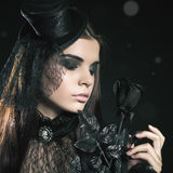 Fashion young woman holding black rose, Halloween party 2016!. Beautiful woman like doll with hat. Halloween costumes. Role. Witch carnival costume. Sexy girls Stock Image