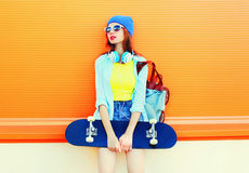 Fashion young woman is holding a skateboard in the city over colorful orange Stock Photography