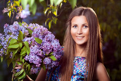 Fashion young woman with lilac flowers Stock Photo