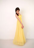 Fashion young woman in long yellow dress, studio Royalty Free Stock Images