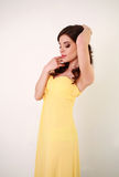 Fashion young woman in long yellow dress, on white Stock Photography