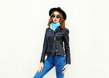Fashion young woman model posing wearing black rock jacket, hat over white Royalty Free Stock Photo