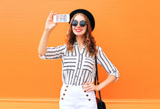 Fashion young woman model taking picture self portrait on smartphone wearing black hat white pants over colorful orange Stock Photo
