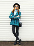 Fashion young woman model wearing black hat checkered coat jacket handbag in city over white Stock Photo