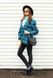 Fashion young woman model wearing black hat checkered coat jacket handbag walking in city over white Royalty Free Stock Photography