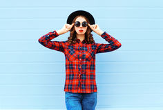 Fashion young woman model wearing black hat, red checkered shirt over blue background. Fashion young woman model wearing a black hat, red checkered shirt over Stock Images