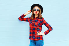 Fashion young woman model wearing a black hat, red checkered shirt over blue background Stock Image